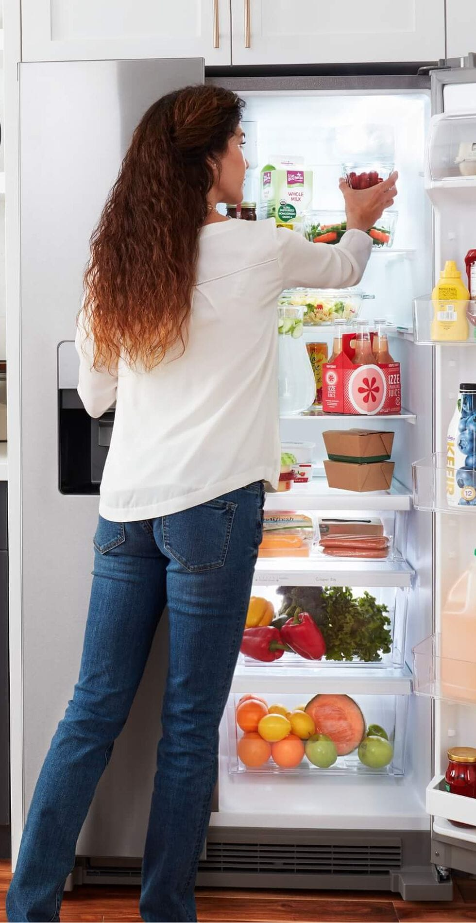 Person opening refrigerator to put away groceries