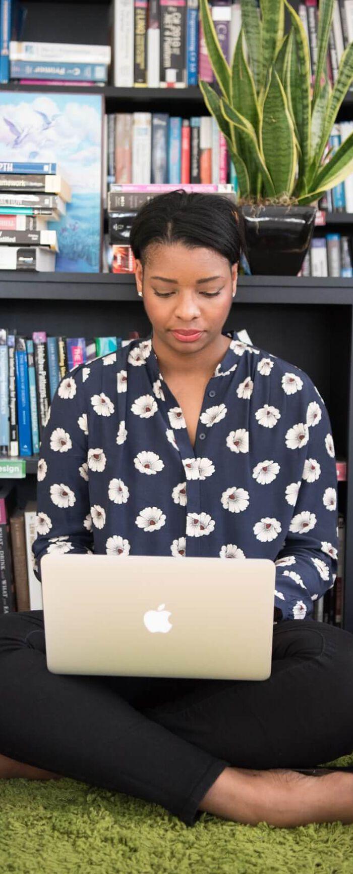 Smiling Woman Working on Laptop Drinking Beverage