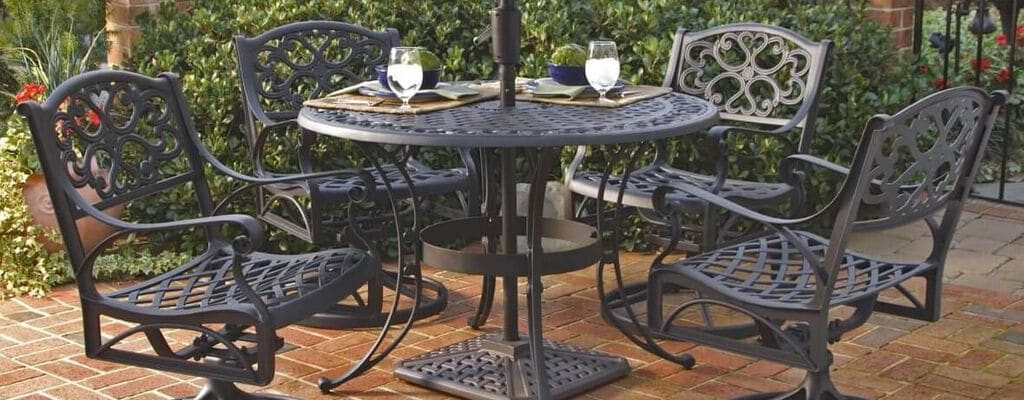 Ornate black metal patio set set on a red brick patio with brown shade umbrella