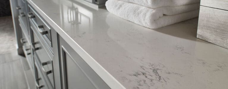 Quartz bathroom countertop with white folding towels on counter