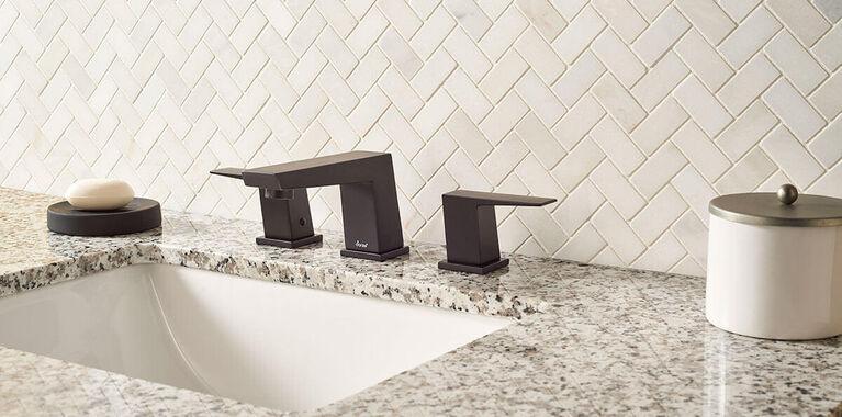 Granite countertop in bathroom with dark bronze faucet