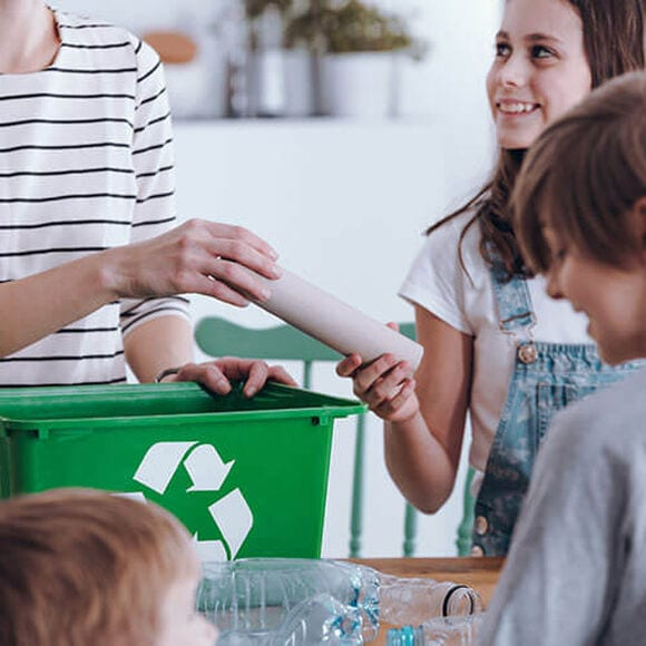 Family gathering together to recycle at their home