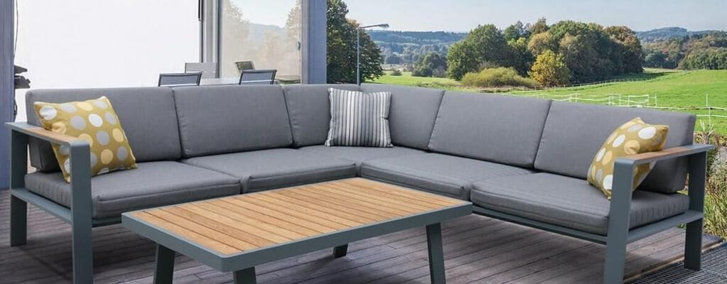 Outdoor Sectional with accent table on Backyard Lanai with sun shining on green field behind home