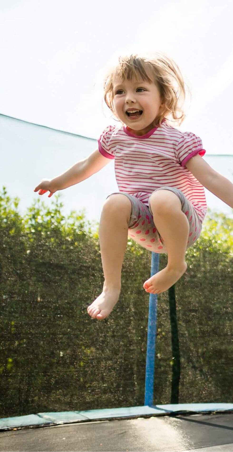 Child jumping on trampoline in backyard