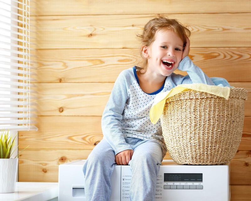 Child laughing while sitting on top of white dryer