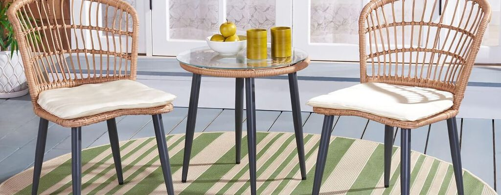 Light tan wicker bistro patio set on backyard porch with coffee table set between two chairs