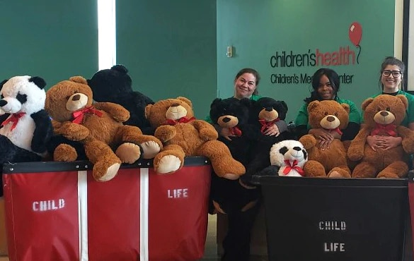 Group surrounded around donated teddy bears