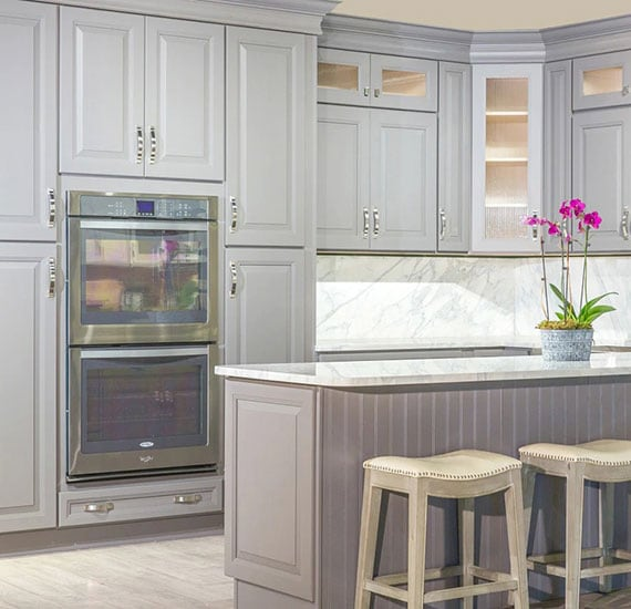 Light gray kitchen cabinets with light granite countertops.